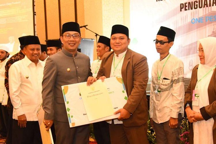 Gubernur Jawa Barat Ridwan Kamil dan Wakil Gubernur Jawa Barat Uu Ruzhanul Ulum menyerahkan hadiah kepada pondok pesantren (ponpes) peserta One Pesantren One Product (OPOP) di Bandung, Selasa (3/9/19).