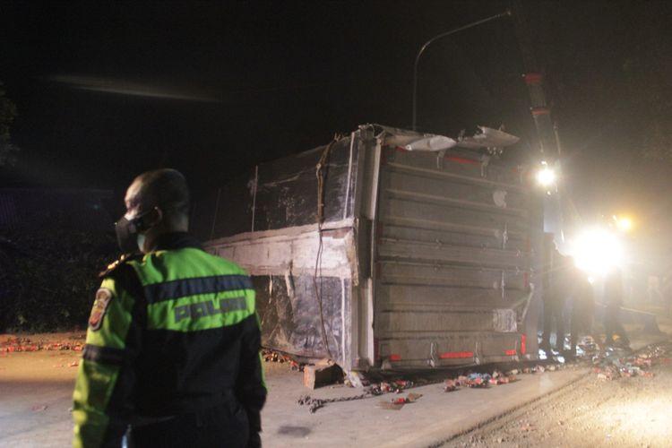 Seorang anggota polisi sedang mengawal proses evakuasi badan truk tronton yang terguling dan menutup badan jalan di jalur Gekbrong, Cianjur, Selasa (28/9/2021). Truk terlibat tabrakan dengan enam kendaraan dan menyebabkan dua orang tewas.