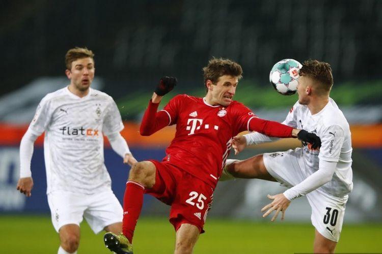 Pemain depan Bayern Munich Thomas Mueller (tengah) dan bek Swiss Moenchengladbach Nico Elvedi (kanan) bersaing memperebutkan bola selama pertandingan sepak bola divisi pertama Bundesliga Jerman Borussia Moenchengladbach v FC Bayern Munich di Moenchengladbach, Jerman barat pada 8 Januari 2021.
