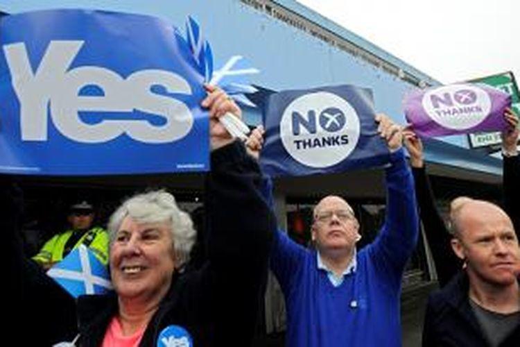 Warga Skotlandia yang mendukung dan menolak kemerdekaan berdiri berdampingan dalam sebuah kampanye politik di Glasgow, Jumat (12/9/2014).