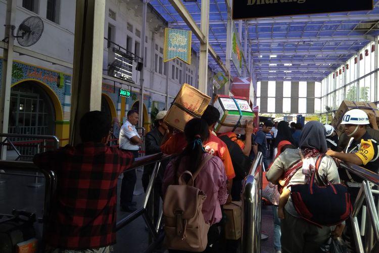 Porter atau pramuantar sedang membawa barang bawaan penumpang di Stasiun Pasar Senen, Rabu (13/6/2018).