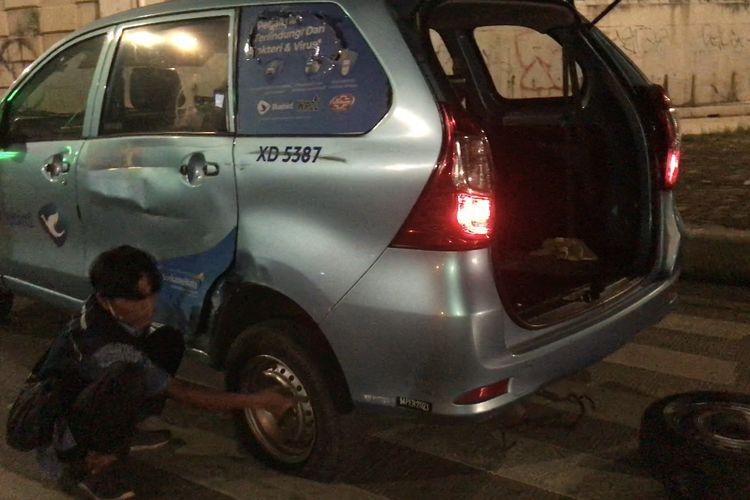 Sopir taksi sedang mengganti ban yang sobek akibat kecelakaan dengan motor di Jalan Raya Sawangan tepatnya di persimpangan Tol Desari, Rangkapan Jaya Baru, Pancoran Mas, Jakarta Selatan pada Minggu (20/6/2021) pagi.
