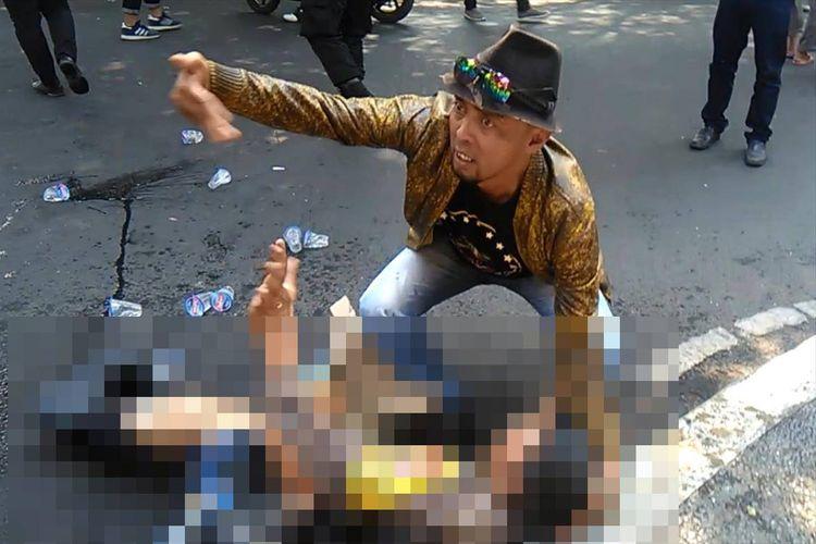 Seseorang coba memberikan pertolongan kepada seorang anggota polisi yang terbakar saat terjadi insiden kericuhan dalam aksi unjukrasa di ruas Jalan Siliwangi depan gerbang Pendopo Bupati Cianjur, Jawa Barat, Kamis (15/08/2019) siang