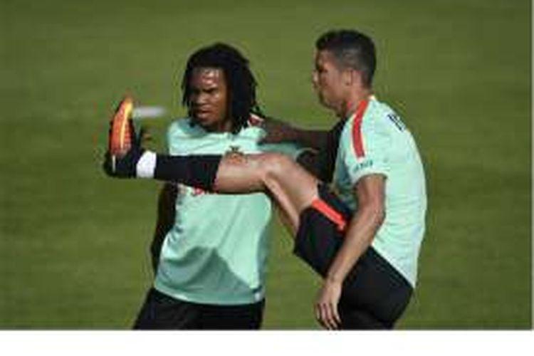 Penyerang Portugal Cristiano Ronaldo (kanan) melakukan peregangan otot dan dibantu gelandang muda Portugal, Renato Sanches, dalam sesi latihan persiapan Piala Eropa 2016 di