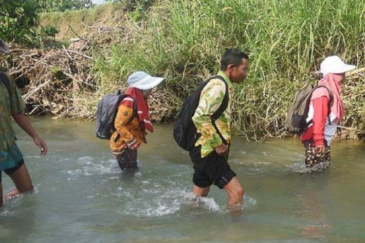 Guru SD Negeri Pojokklitih 3, Kecamatan Plandaan, Jombang, (dari kiri ke kanan) Sucipto, Laila Maulida, Trisno, dan Nurmala Sari, menyeberangi sungai untuk mengajar, Kamis (23/3/2017).