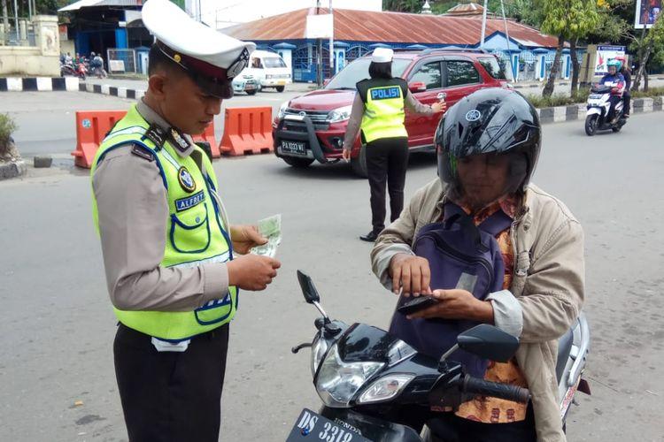 Seorang anggota lalu lintas saat memeriksa surat kendaraan dari pengendara sepeda motor saat Operasi Zebra Matoa 2018, di Papua.
