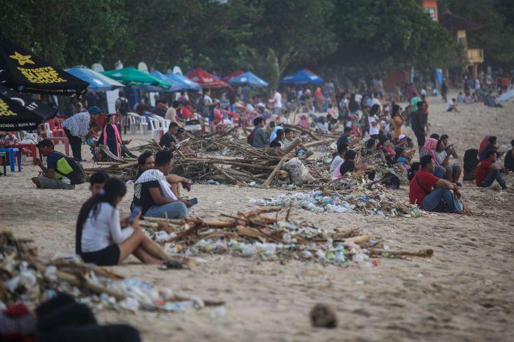 Wisatawan duduk di samping tumpukan sampah saat musim angin barat di pesisir pantai Kuta, Bali, Jumat (14/12/2018). Akibat terjadinya musim angin barat di wilayah perairan Bali berdampak pada banyaknya sampah yang hanyut terbawa arus laut sehingga menumpuk di pinggiran pantai kawasan wisata kuta.