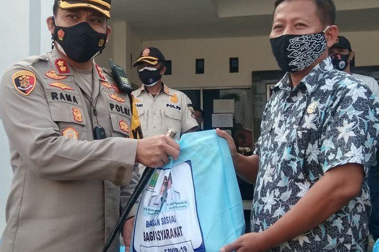 Kepala Polisi Resor (Kapolres) Karawang AKBP Rama Samtama Putra (kiri) secara simbolis menyerahkan paket sembako kepada kepala desa di Kecamatan Cilamaya Wetan, Kabupaten Karawang.