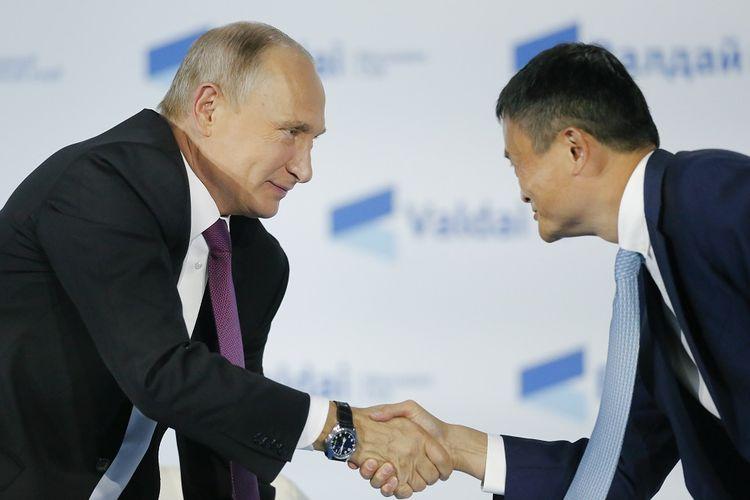 Presiden Rusia Vladimir Putin (kiri) berjabat tangan dengan pendiri raksasa e-commerce Alibaba Jack Ma di Sochi pada 19 Oktober 2017.