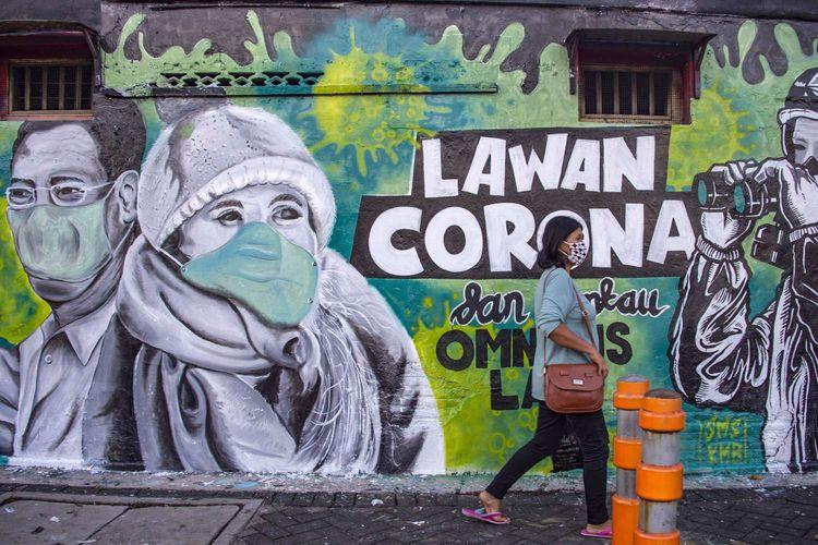 Seorang wanita melintas di depan mural yang mengajak orang untuk melawan virus corona di Surabaya, 26 Maret 2020. Pandemi Covid-19 yang disebabkan oleh virus corona menjadi insipirasi seniman grafiti atau mural untuk memberikan peringatan dan motivasi bagi warga dalam menghadapi virus tersebut.