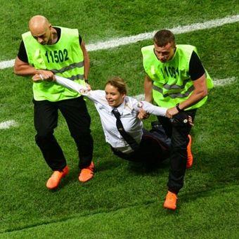 Anggota kelompok Pussy Riot, diaman oleh petugas keamanan pada pertandingan final Piala Dunia 2018  di Stadion Luzhniki di Moskwa, Rusia, Minggu (25/7/2018). (AFP/Mladen Antonov)