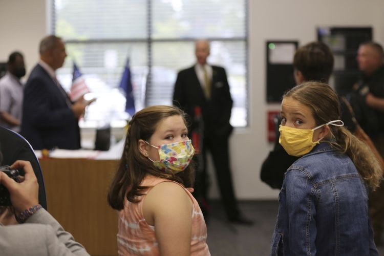 Dua murid Camden Elementary School, Amerika Serikat, mengenakan masker saat mendengarkan pidato Gubernur South Carolina, Henry McMaster, tentang cara sekolah menangani Covid-19, pada Rabu (15/9/2021).