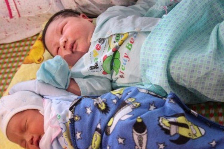 Tran Tien Quoc (atas) sedang tidur di samping bayi laki-laki. Tran Tien Quoc dinobatkan sebagai salah satu bayi terberat di Asia Tenggara