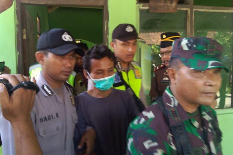 Anal Rojikun (memakai masker), tersangka perusakan masjid dan TPQ di Desa Buniayu,Kecamatan Tambak, Kabupaten Banyumas, Jateng, diminta menunjulkan lokasi yang menjadi sasaran aksinya, Jumat (22/3/2019).