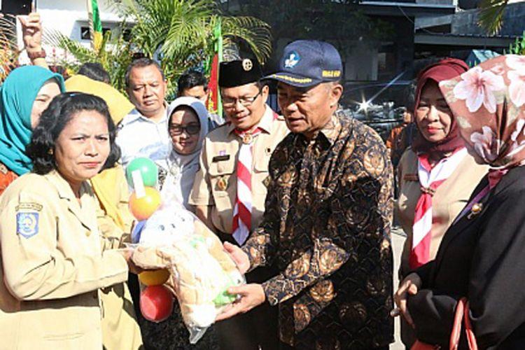 Menteri Pendidikan dan Kebudayaan (Mendikbud) Muhadjir Effendy sedang memberikan bantuan kepada lembaga PAUD yang terkena dampak bencaba gempa di Lombok (15/8/2018)