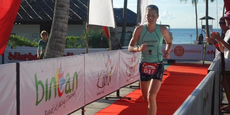 Seorang triatlet, berlari memasuki garis finis pada Metaman Bintan Triathlon 2013 di Nirwana Garden Resort, Bintan, Riau, Sabtu (31/8/2013).