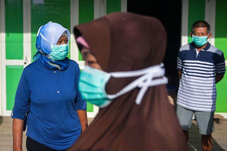 Warga beraktivitas menggunakan masker di Kota Tua Penagi, Natuna, Kepulauan Riau, Kamis (6/2/2020). Bupati Natuna Abdul Hamid Rizal menyatakan bahwa warga dalam keadaan sehat dan tidak ada yang eksodus meskipun lokasinya berada di sekitar kurang lebih satu kilometer dari tempat diobservasinya 238 WNI pascaevakuasi dari Wuhan, Hubei, China yang memasuki hari kelima.