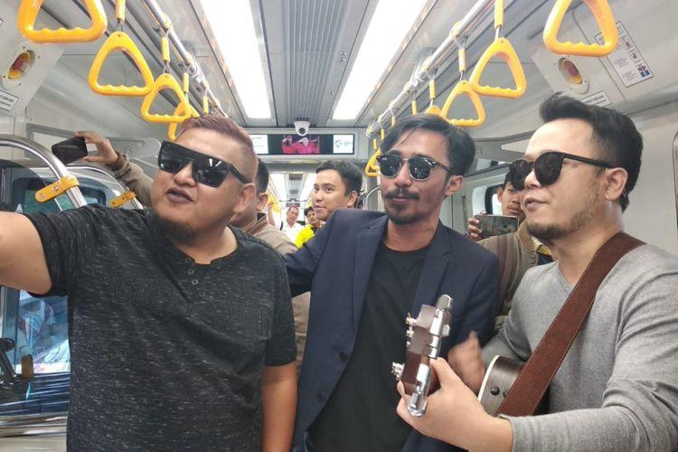 ST12 Zai (Vokalis), Indra (Bassis), dan Pepep (Gitaris/keyboardist) saat mengamen di dalam kereta light rail transit (LRT) Palembang, Sumatera Selatan, Kamis (20/9/2018). Usai ngamen di LRT Palembang, ST 12 berencana untuk membuat video klip.