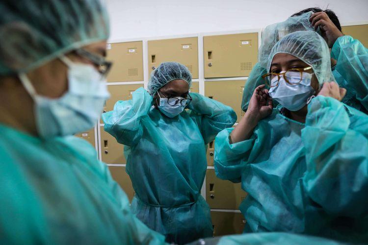 Wartawan memakai alat pelindung khusus, seperti sendal karet, baju pengaman khusus, dan masker untuk memasuki laboratorium yang memeriksa sampel media pembawa virus Corona untuk penelitian di Laboratorium Penelitian Penyakit Infeksi Sri Oemijati, Jl. Percetakan Negara, Jakarta Pusat, Selasa (11/2/2020). Total ada 64 spesimen yang dikirim ke lab Badan Litbangkes, 2 kasus diantaranya masih dalam pemeriksaan, sedangkan 62 lainnya negatif virus corona.