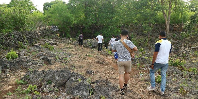 Wisatawan berjalan ke mulut Goa Kristal di Desa Bolok, Kecamatan Kupang Barat, Kabupaten Kupang, Nusa Tenggara Timur, Minggu (9/12/2018). Keindahan air yang berwarna biru muda dan tua di Goa Kristal siap memikat wisatawan yang datang.