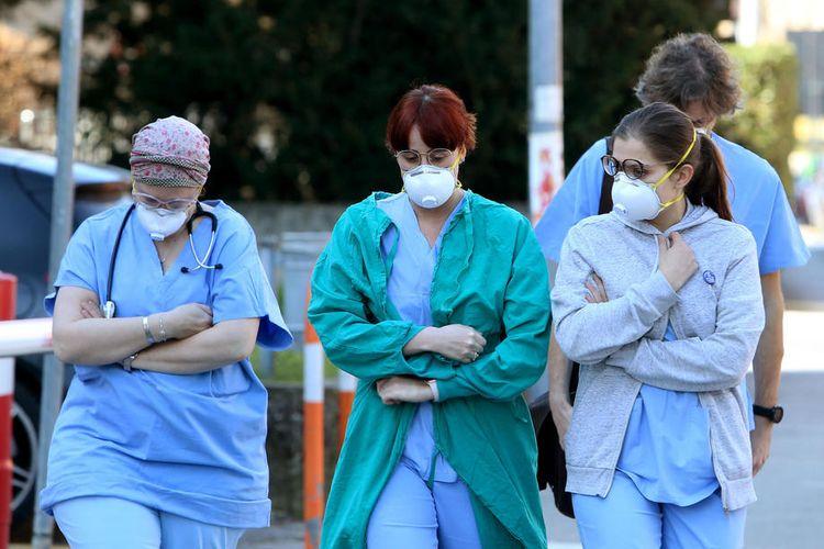 Orang-orang dan petugas kesehatan memakai masker wajah pelindung di luar rumah sakit di Padua, wilayah Veneto, Italia utara  EPA-EFE/NICOLA FOSSELLA
