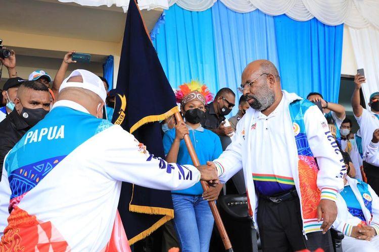 Gubernur Papua, Lukas Enembe, menyerahkan Pataka Kontingen PON Papua kepada Kapolda Papua, Irjen Mathius D Fakhiri, yang ditunjuk sebagai Ketua Kontingen PON Papua pada PON XX 2021, Jayapura, Papua, Kamis (9/9/2021)