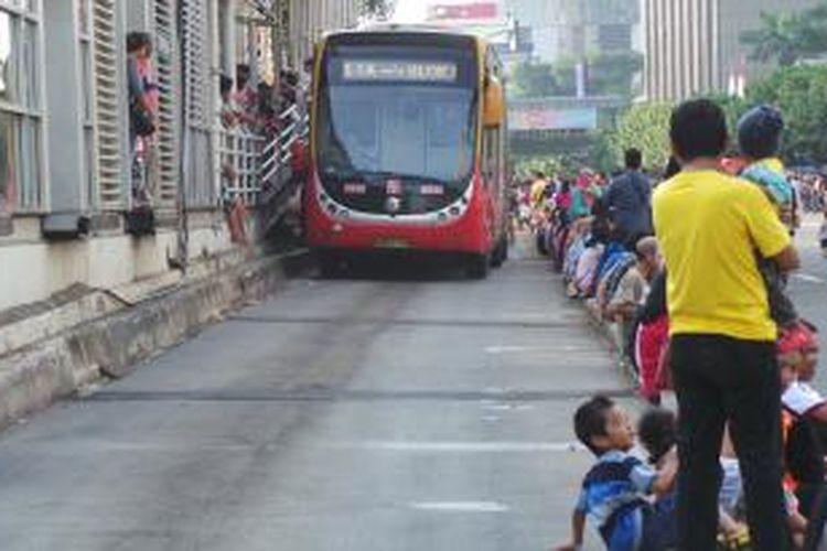 Pemandangan pengunjung Jakarnaval yang duduk di sepanjang sparator buswat Koridor I, di kawasan Jalan MH Thamrin, Jakarta Pusat. Minggu (22/6/2014). Transjakrta tetap beroperasi di acara Jakarnaval ini.