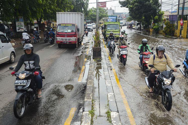 Sejumlah pengendara motor melintasi jalan Sultan Agung yang diberlakukan sistem contraflow akibat banjir di Bekasi, Jawa Barat, Selasa (21/1/2020). Banjir setinggi 20 cm diakibatkan oleh saluran drainase yang buruk sehingga menyebabkan kemacetan di sejumlah jalan raya Bekasi.