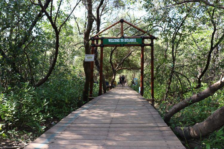 Jembatan kayu dan gerbang selamat datang di hutan mangrove pantai Glagah Wangi Istambul, Demak, Jawa Tengah