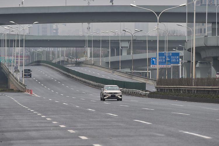 Sebuah mobil melintas di jalanan kota Wuhan, China, yang sepi karena wabah virus corona yang mematikan di hari pertama tahun baru Imlek, Sabtu (25/1/2020).