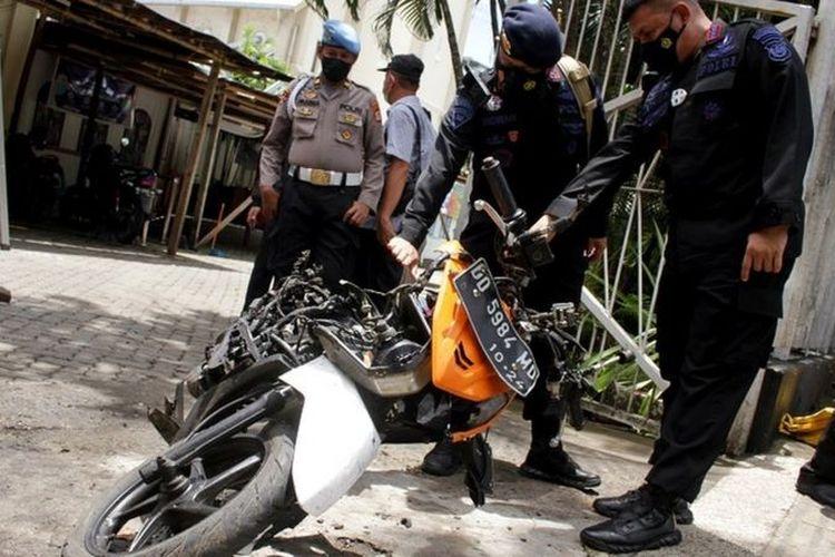 Anggota polisi mengamati motor yang digunakan terduga pelaku bom bunuh diri sebelum dievakuasi di depan Gereja Katedral Makassar, Sulawesi Selatan, Senin (29/3/2021).