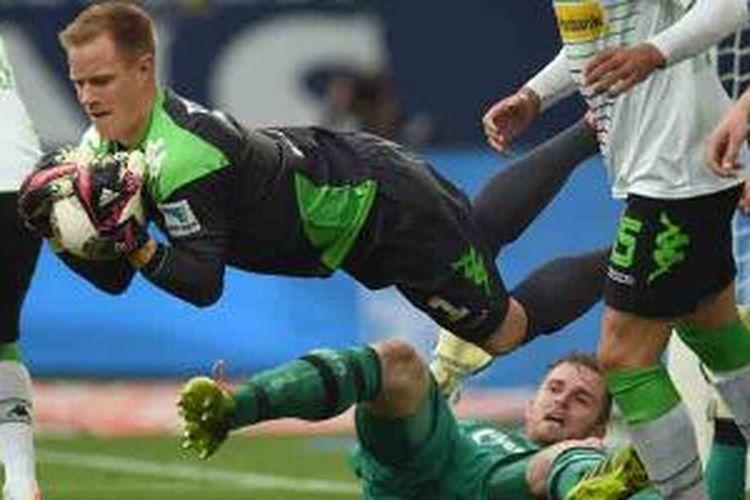 Penjaga gawang Borussia Moenchengladbach, Marc-Andre ter Stegen, menangkap bola setelah menang duel dengan penjaga gawang Schalke, Ralf Faehrmann, yang membantu serangan saat terjadi tendangan pojok di menit terakhir laga kedua tim.
