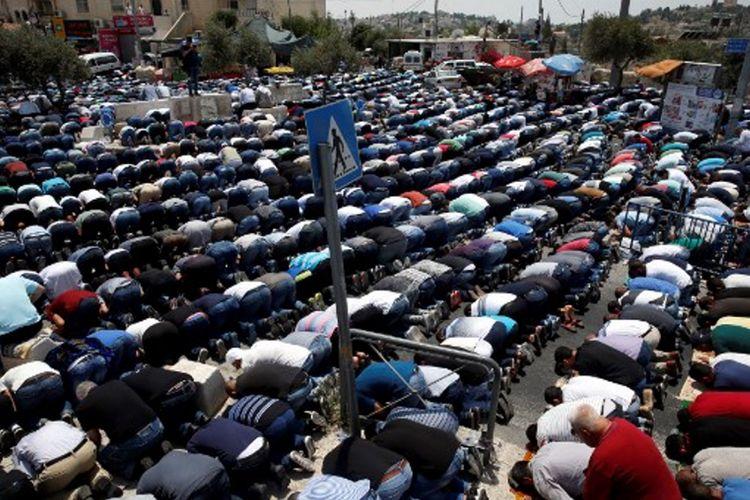 Warga Palestina menjalankan ibadah Shalat Jumat di luar pintu masuk menuju kawasan Kota Tua Yerusalem di depan Masjid Al-Aqsa, Jumat (21/7/2017).  Israel melarang pria Palestina yang berusia di bawah 50 tahun untuk masuk ke kawasan Kota Tua dan menjalani Shalat Jumat, menyusul insiden penembakan dua polisi Israel.