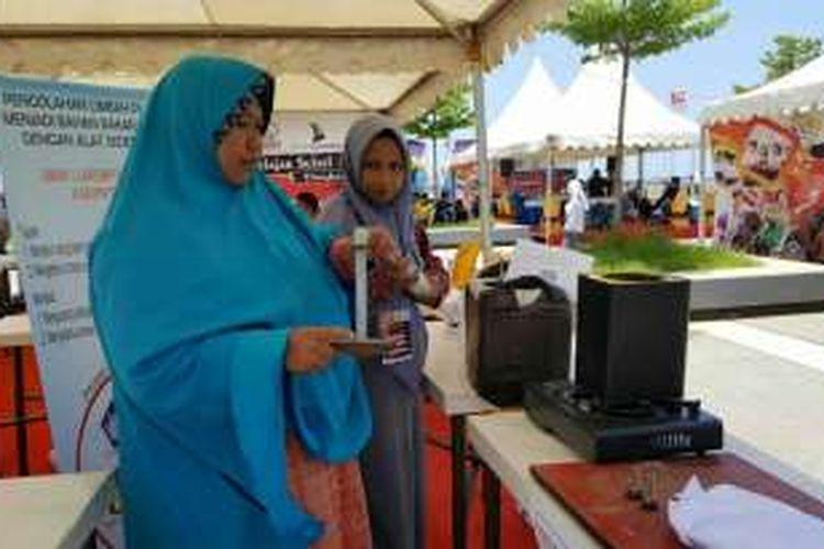 Siswa SMK Negeri 1 Larompong, Kabupaten Luwu didampingi gurunya memamerkan olahan limbah plastik menjadi bahan bakar di festival pelajar yang digelar di Anjungan Pantai Losari, Makassar, Sabtu (15/10/2016).