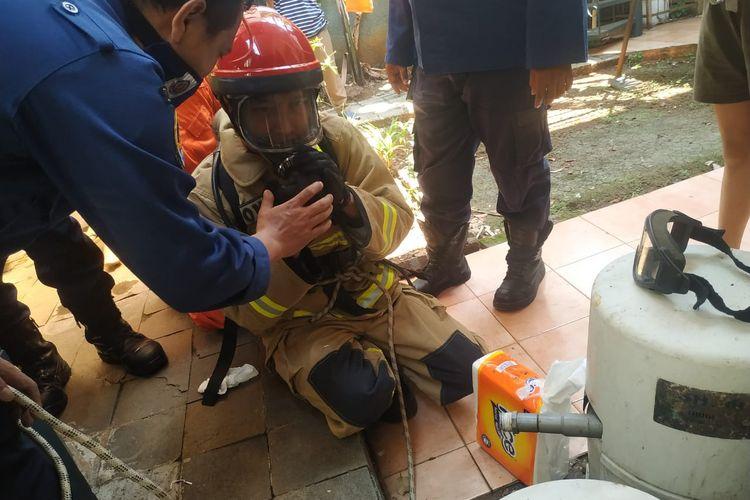 Pandu Wirastomo (24), anggota Suku Dinas Penanggulangan Kebakaran dan Penyelamatan (Sudin Gulkarmat) Jakarta Selatan Sektor V Cilandak memakai Alat Pengaman Dasar (APD) sempat kesulitan bergerak saat menyelamatkan seekor kucing kampung di dalam sumur sedalam 8 meter.