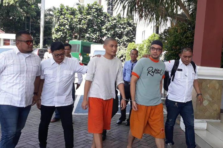 Artis peran Sandy Tumiwa (kedua dari kanan) menjalani proses pemindahan tahanan di Kejaksaan Negeri Jakarta Pusat, Kemayoran, Rabu (19/6/2019).