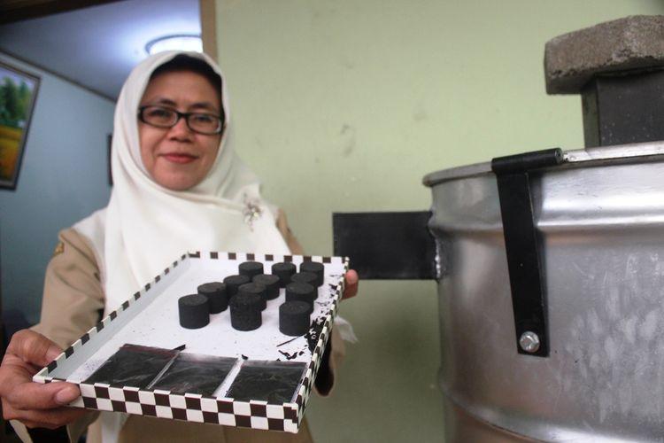 Nenden Raspati, perempuan paruh baya asal Cianjur, Jawa Barat memerlihatkan sejumlah produk turunan dari hasil pembakaran sampah di dalam alat yang dibuatnya.