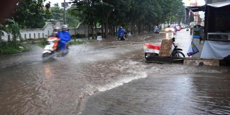Pengendara roda dua di Jalan Mastrip, Kabupaten Jember, Jawa Timur, yang memaksa menerobos banjir, akhirnya motornya mogok, Jumat (6/3/2015).