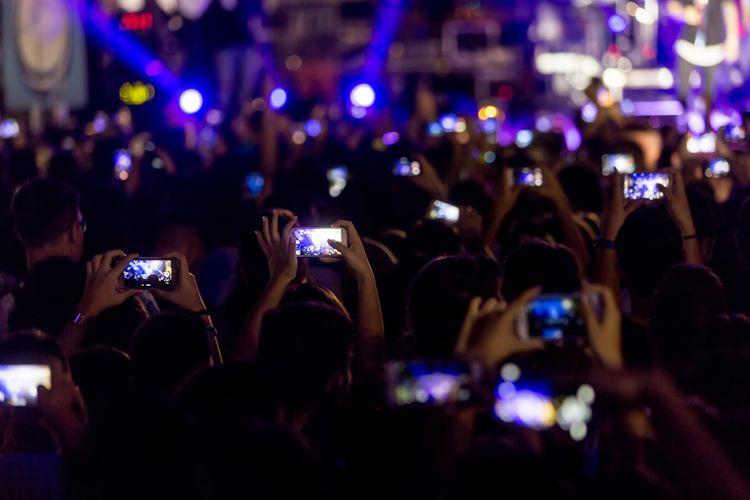 Ilustrasi penonton memotret pertunjukan konser menggunakan kamera ponsel.