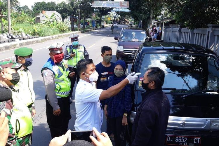 Petugas gabungan TNI, Polri dan unsur Pemerintah Kota Tasikmalaya sedang melakukan pemeriksaan para pemudik di salah satu pos penjagaan perbatasan wilayah Kecamatan Indihiang, Kota Tasikmalaya, Rabu (22/4/2020).