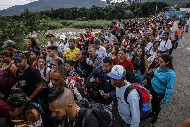 Warga Venezuela mengantre pemeriksaan dokumen di perbatasan dengan Kolombia, Minggu (9/6/2019).