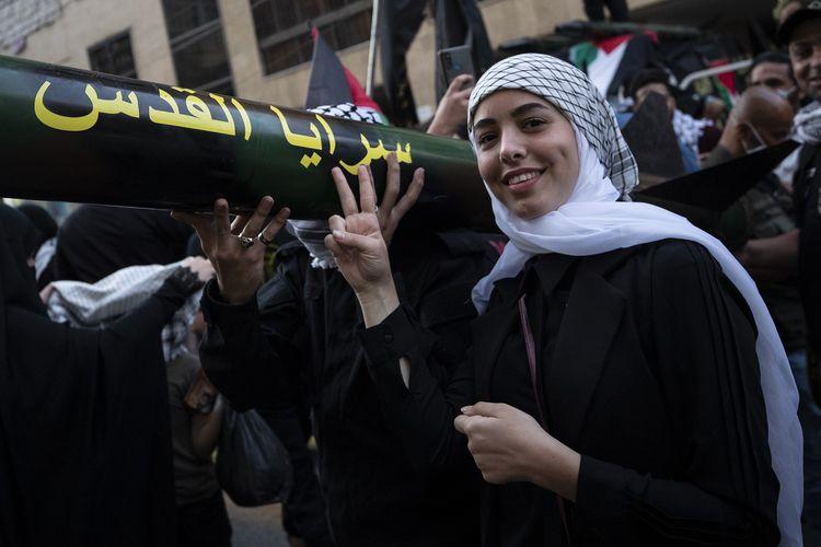 Seorang gadis berpose di samping replika roket, selama demonstrasi yang diorganisasi Hezbollah, di pinggiran selatan Beirut, Lebanon, pada 17 Mei 2021.
