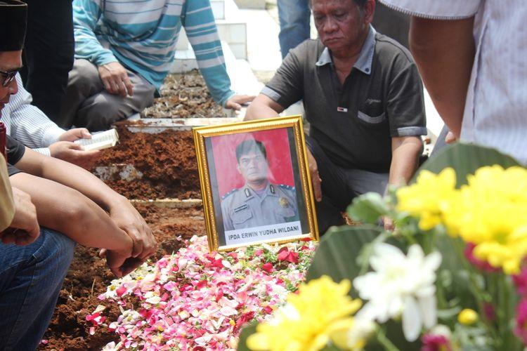 Keluarga dan kerabat berdoa di atas kuburan Ipda Erwin Yudha Wildani (45) di Taman Makam Pahlawan Cikaret, Cianjur, Jawa Barat, Senin (26/08/2019)