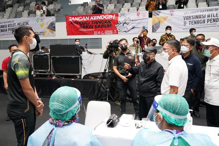 Wakil Presiden Ma'ruf Amin berbincang dengan atlet bulutangkis Indonesia Jonatan Christie yang akan melaksanakan vaksinasi Covid-19 di Istora Senayan, Jakarta, Jumat (26/2/2021).