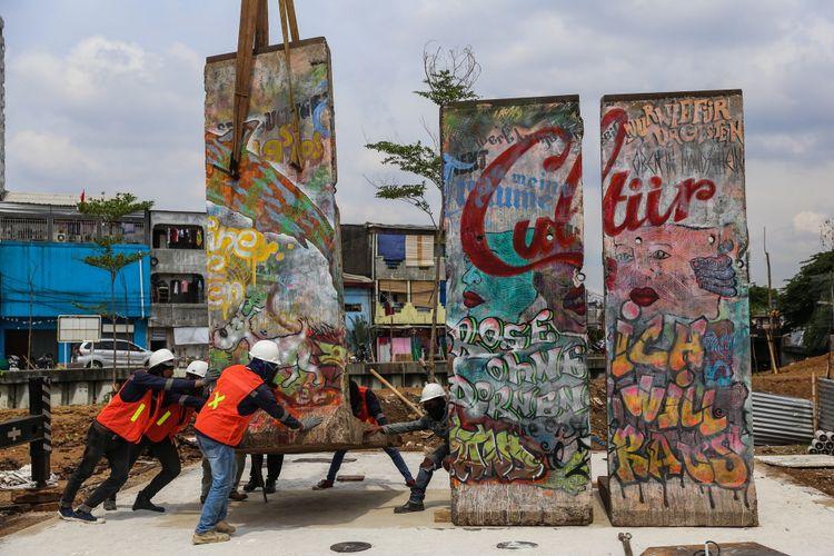 Sejumlah pekerja melakukan pemasangan batu pecahan tembok berlin di kawasan Ruang Publik Terpadu Ramah Anak (RPTRA) dan Ruang Terbuka Hijau (RTH) Kalijodo, Jakarta Barat, Selasa (26/9/3017). Karya seni instalasi ini bernama Patung Menembus Batas terdiri dari empat pecahan tembok Berlin dan 14 patung baja hasil karya dari seniman Teguh Osternik.