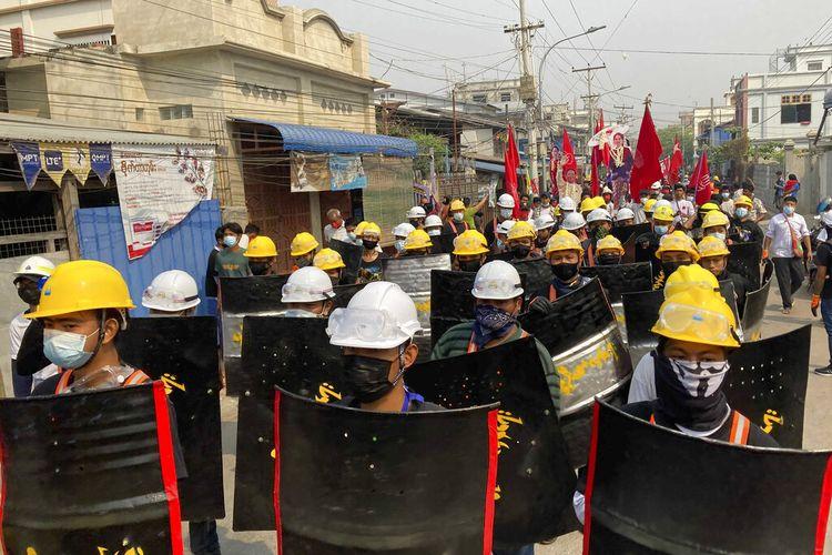 Para pengunjuk rasa berbaris dengan perisai buatan tangan di jalan utama selama demonstrasi di Mandalay, Myanmar, Senin (8/3/2021). Aksi protes besar-besaran terjadi setiap hari di banyak kota besar dan kecil di Myanmar.