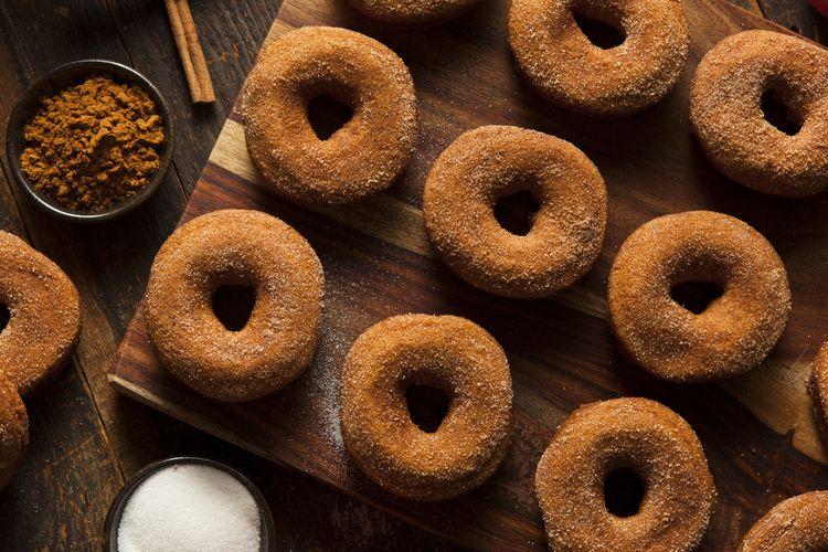 Ilustrasi donat goreng topping gula dan kayu manis bubuk.
