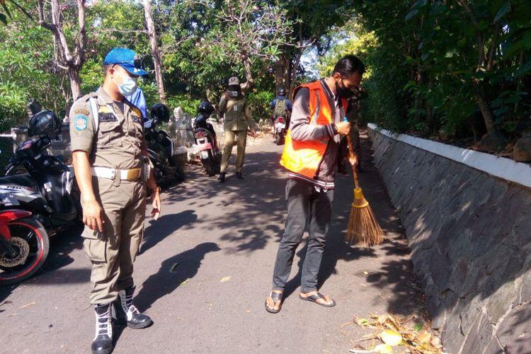 Warga Semarang diberi sanksi menyapu karena melanggar protokol kesehatan.