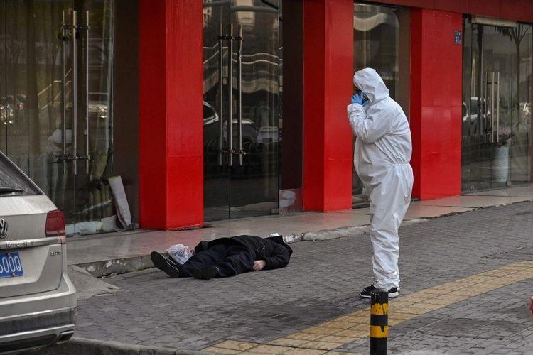 Seorang petugas medis terlihat memandangi mayat pria yang terbaring di depan toko furnitur di Wuhan, China, pada 30 Januari 2020. Jurnalis AFP yang mengambil gambarnya tidak bisa mengonfirmasi bagaimana meninggalnya. Namun, pengguna jalan meyakini dia meninggal karena terinfeksi virus corona.