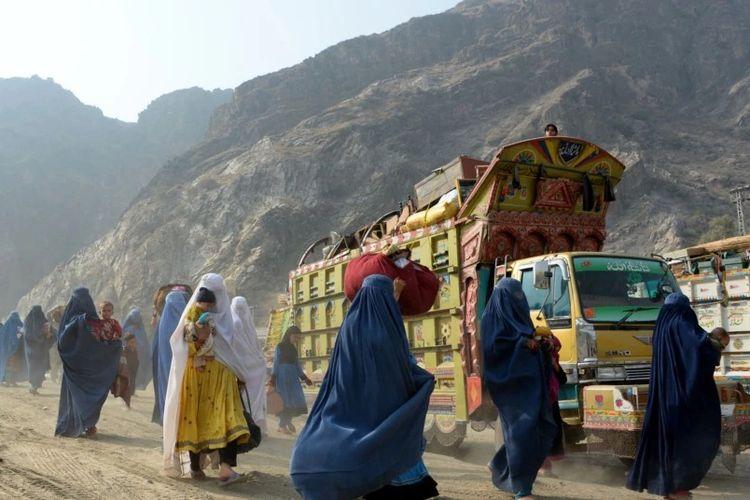 Pengungsi Afghanistan berpakaian burqa tiba di pusat repatriasi Komisaris Tinggi PBB untuk Pengungsi (UNHCR) di Torkham, saat mereka melintasi perbatasan utama antara Afghanistan dan Pakistan untuk kembali ke negara asal mereka. [NOORULLAH SHIRZADA/AFP VIA VOA INDONESIA]